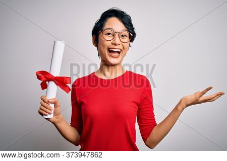 Beautiful chinese student woman wearing glasses holding university graduated diploma degree very happy and excited, winner expression celebrating victory screaming with big smile and raised hands