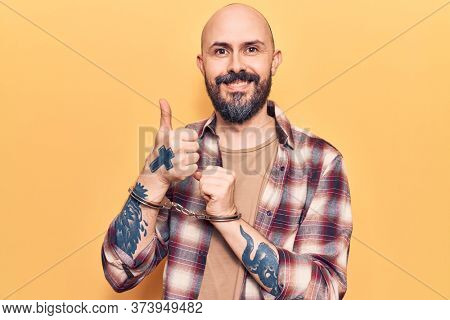 Young handsome man wearing prisoner handcuffs smiling happy and positive, thumb up doing excellent and approval sign