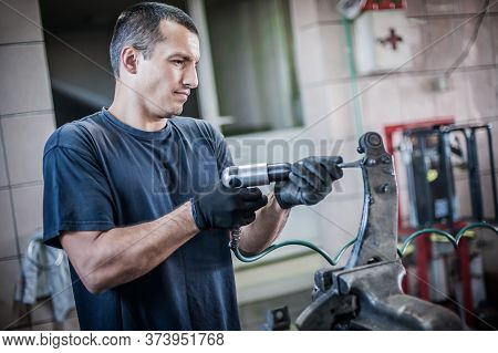 Car Mechanic Working In Auto Vulcanizing And Vehicle Service Workshop