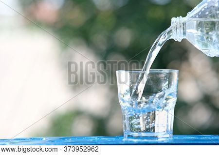 Glass Of Water On Wood Table Background And Pouring Drinking Water
