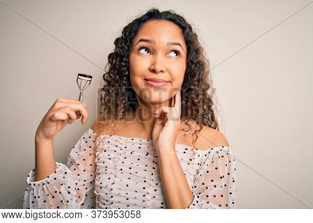 Young beautiful woman with curly hair holding eyelases curler over white background serious face thinking about question, very confused idea
