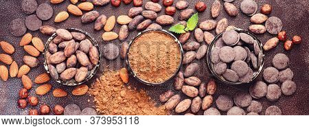 Cocoa Beans, Cocoa Powder, Nuts And Dark Chocolate On A Rustic Background, Banner. Top View, Flat La