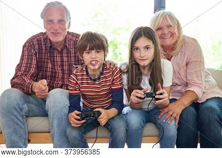 Kids with game console playing video game together with grandparents