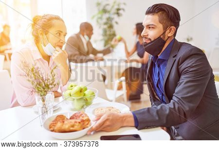 Businessmen flirt with mouthguards under the chin in the Café during break after Covid-19 and Coronavirus pandemic
