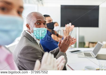 Business people with face mask donate applause in a seminar on video communication