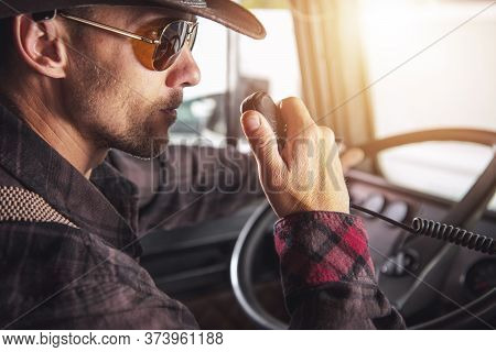 Caucasian Male Truck Driver Sitting In Cab Of Vehicle Talking On Two Way Radio.