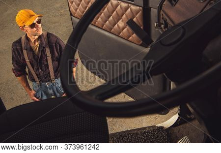 Middle Age Male Trucker Standing Outside Of Vehicle Cab And Looking Around.