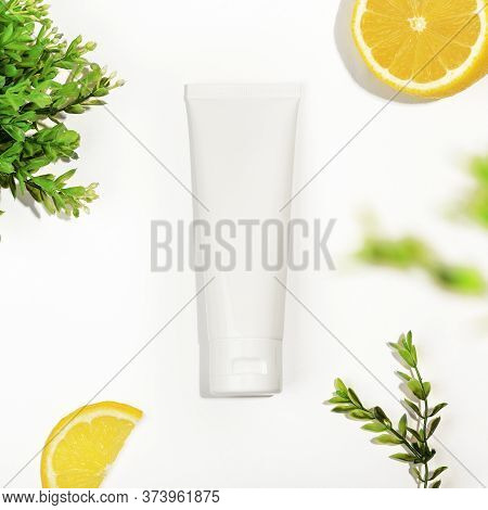 Top View Of White Plastic Tube With Lemon And Green Plant. Unbranded Tube For Cream, Scrub, Lotion O