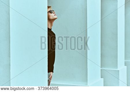 Fashion shot. Handsome young man model in black pullover and black sunglasses posing next to white columns in the old town. Men's style, beauty. Art portrait.
