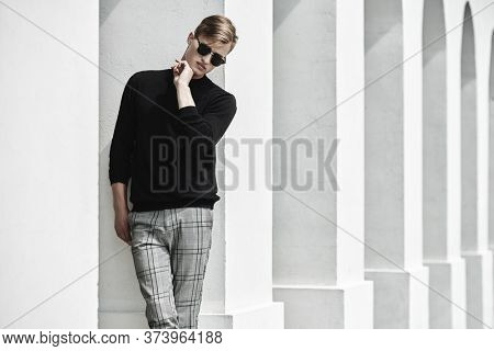 Fashion shot. Handsome young man model in black pullover, plaid trousers and black sunglasses posing next to white columns in the old town. Men's style, beauty.