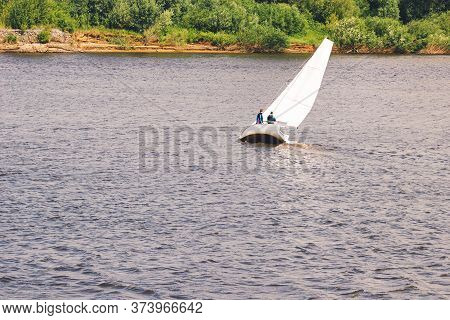 Yacht With White Sails At Volga River. Sailboat Tilted In A Gust Of Wind. Boat With A Sail Is Sinkin