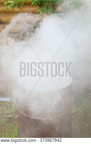 Garbage Incineration In Rusty Metal Barrel With Release Of Large Amount Of Smoke. Harm To Environmen