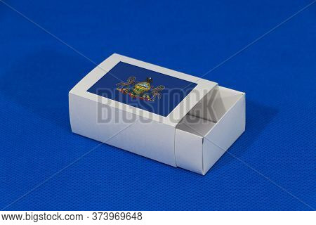 Pennsylvania Flag On White Box On Blue Background, Paper Packaging For Put Match Or Products. The Co