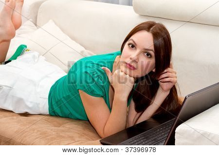 Attactive Woman Lying On The Sofa With Laptop