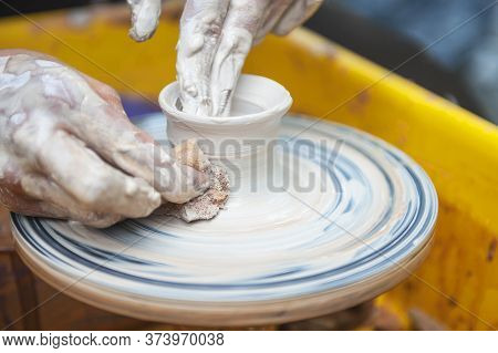 The Potter Makes Pottery Dishes On Potter's Wheel.