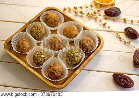 Homemade Vegan Candy Balls From Nuts, Dates, Seeds, Cocoa Free Sugar On A Wooden Plate On A White Ba