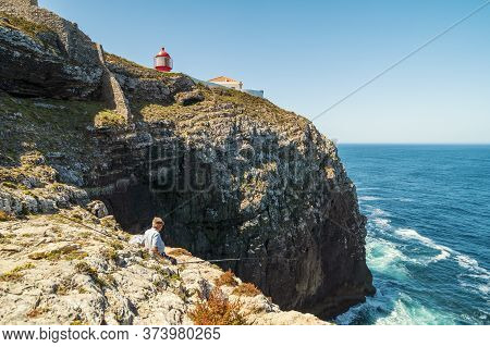 Elderly Man Fishing With A Rod On High Cliffs Of Sao Vicente Cape, Portugal