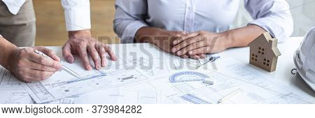 Construction Engineering Or Architect Discuss A Blueprint While Checking Information On Drawing And