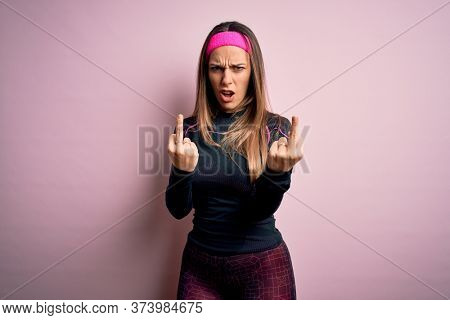 Young blonde fitness woman wearing sport workout clothes over isolated background Showing middle finger doing fuck you bad expression, provocation and rude attitude. Screaming excited
