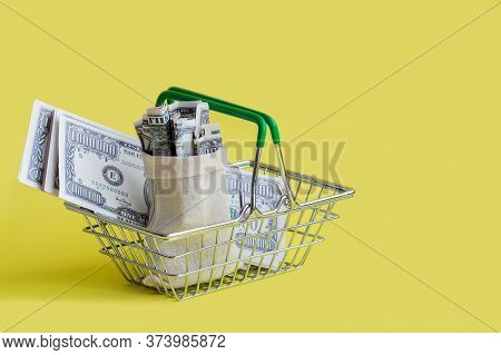 Metal Shopping Basket With Green Handles, With A Canvas Bag Filled With Money And Banknotes On A Yel