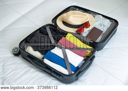 Luggage For Summer Vacation. Travel Accessories In Suitcase On The Bed. Time To Travel, Relaxation,