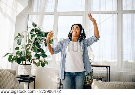 Woman in headphones listen to music and dancing