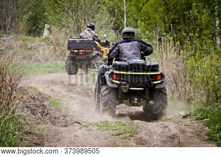 Selective Focus. Two Riders On Atvs Ride On A Dirt Road. The Concept Of Outdoor Activities And Extre