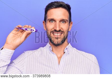 Young handsome man controlling temperature holding thermometer over purple background looking positive and happy standing and smiling with a confident smile showing teeth