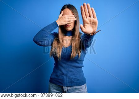 Young beautiful blonde woman with blue eyes wearing glasses standing over blue background covering eyes with hands and doing stop gesture with sad and fear expression. Embarrassed and negative