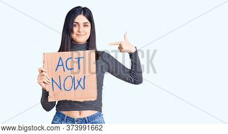 Young beautiful girl holding act now cardboard banner pointing finger to one self smiling happy and proud