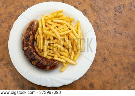 Grilled Sausage, German Bratwurst, And French Fries On A Plate In A Fast Food Restaurant, Tasty But
