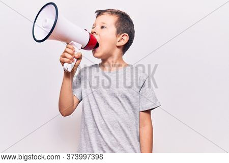 Adorable caucasian kid boy with angry expression. Screaming loud using megaphone standing over isolated white background