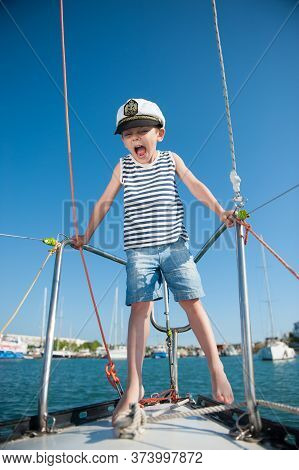 Angry Small Boy In Captain White Hat Striped Tank Top And Jeans Shorts Shouting On Luxury Sea Yacht