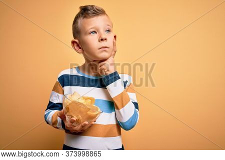 Young little caucasian kid eating unheatlhy potatoes crisps chips over yellow background serious face thinking about question, very confused idea