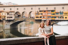 Happy Family Mother And Daughter Against The Backdrop Of The Ponte Vecchio Bridge In Florence.family