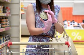 Woman Wears Protective Mask And Gloves While Shopping At Supermarket. Holding A Tin Can. Pandemic Ti