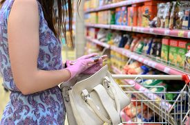 Woman Wears Protective Gloves While Shopping At Supermarket. Holding A Smartphone In His Hands. Pand