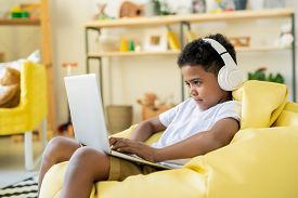 Concentrated adorable schoolkid in headphones looking at laptop display while playing game or taking online educational course