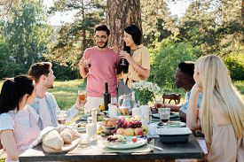 Happy young intercultural couple with glasses of red wine announcing their engagement to friends gathered by served table for outdoor dinner