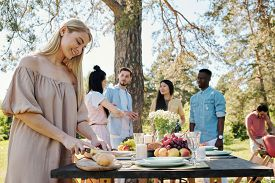 Happy young blond woman cutting fresh baguette on wooden board by table served for dinner on background of talking friends