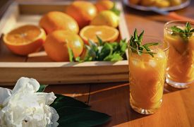 Orange Juice In Crystal Glasses With Mint Leaves And Ice Cubes. Fresh Citrus Juice And Oranges On A