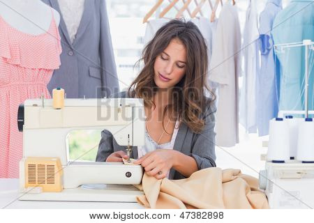 Fashion designer sewing with sewing machine