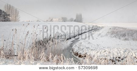 Snowfall Over A Rural Area With A Meandering Ditch