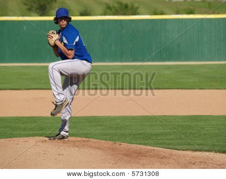 action shot of a high school baseball pitcher winding up to throw the baseball poster