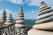 four giant stone stacks against sky on beach poster