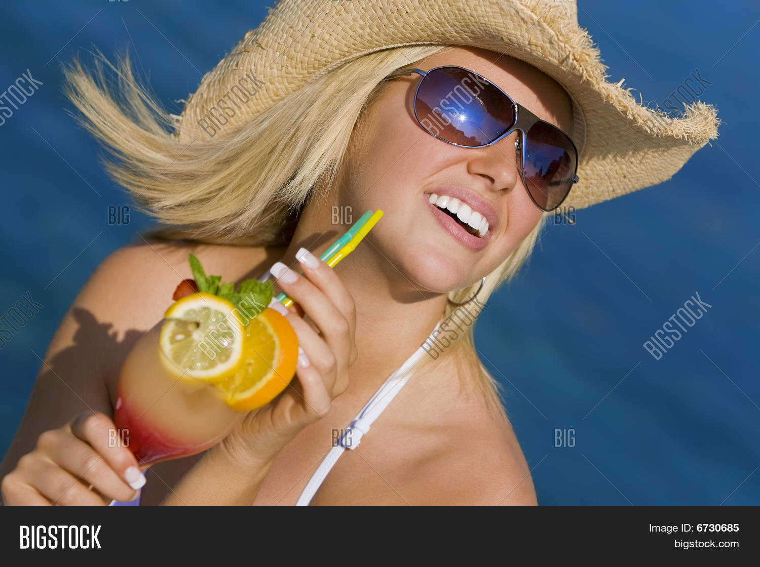 69afbaafa1425 Stunningly beautiful young blond woman in straw cowboy hat and sunglasses  enjoying a cocktail by a deep blue sea