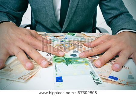 man in suit sitting in a desk full of euro bills trying to hold them depicting wealth or greediness