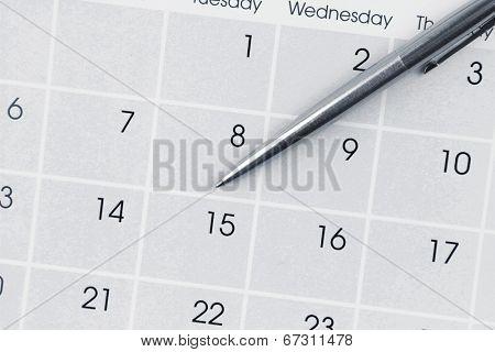 Pen on calendar page closeup