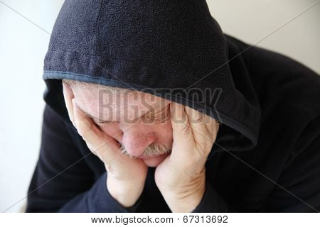 Dejected Senior Man In Hooded Jacket