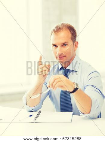 handsome businessman with spectacles showing warning gesture poster